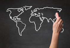 Adult drawing world map on chalkboard Royalty Free Stock Photo