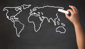 Adult drawing world map on chalkboard Stock Photo