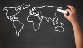 Adult drawing world map on chalkboard Stock Photo