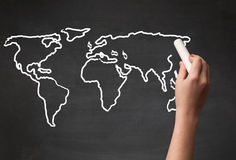 Adult drawing world map on chalkboard Royalty Free Stock Photography