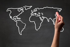 Adult drawing world map on chalkboard. A teacher drawing the map of the world on a blackboard with a chalk Stock Image