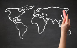 Adult drawing world map on chalkboard Stock Photos