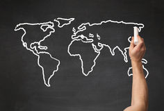 Adult drawing world map on chalkboard Royalty Free Stock Photos