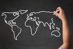Adult drawing world map on chalkboard. A teacher drawing the map of the world on a blackboard with a chalk Royalty Free Stock Photos