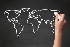 Adult drawing world map on chalkboard. A teacher drawing the map of the world on a blackboard with a chalk Stock Images