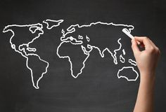 Adult drawing world map on chalkboard. A teacher drawing the map of the world on a blackboard with a chalk Royalty Free Stock Photo