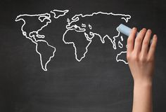 Adult drawing world map on chalkboard Stock Images