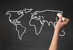 Adult drawing world map on chalkboard. A teacher drawing the map of the world on a blackboard with a chalk Stock Photos