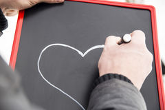 Adult draws heart on the blackboard with white marker Royalty Free Stock Photos
