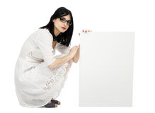 Summer Dress Woman Crouching Next to Sign. An adult (early 30's) black haired caucasian woman, wearing a lovely white summer dress. She's crouching and holding a Stock Image