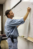 Adult Ed Teacher Vertical. Handsome adult education teacher writing math problems on the board.  Vertical View Stock Images
