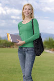 Adult Education. Young woman happily returning to school with her supplies Stock Photo