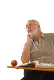 Adult education. Older scholar sitting at a desk with a book; isolated on white Stock Photo