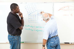 Adult Education - Advanced Mathematics. Teacher and adult student at the board working trigonometry equations.  Focus on the equations on the board Stock Photography