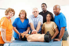 Adult Education Class - First Aid - Serious. Diverse adult education class practicing CPR on a mannequin. Serious expressions stock photos