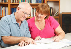 Adult Education Couple. Adult students studying together in the library Royalty Free Stock Photography
