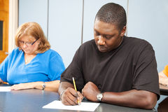 Adult Education - Diversity. Diverse adult education students taking a test in class stock photography