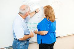 Adult Education - Teaching Math. Adult education student working math equations on the board, with her teacher\'s help Royalty Free Stock Photos