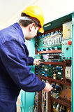 Adult electrician builder engineer worker testing electronics in switch board royalty free stock photo