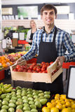 Adult employee of farm food store with fruits Royalty Free Stock Photos