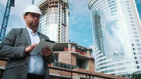 Adult engineer or architect uses a tablet in operation. Writes a message or checks a drawing. Against background is stock footage