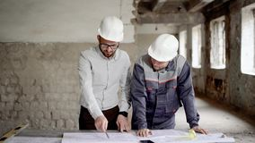 An adult engineer explains to the worker a new construction plan, which was designed by the architect, people are in an