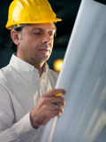 Adult engineer holding blueprints. Middle aged man working as architect and reading building plan in office Stock Image