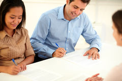 Adult ethnic couple signing a contract Stock Image