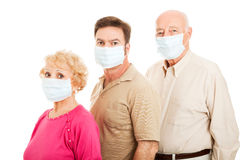 Adult Family - Flu Protection. Senior couple and their adult son wearing surgical masks to protect from flu epidemic.  Isolated Royalty Free Stock Photos