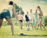 Adult family with four kids running after ball. Adult family with four kids playfully running after ball outdoors on green lawn in park. Focus on teenager girl Royalty Free Stock Photos