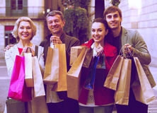 Adult family of four with shopping bags Stock Image