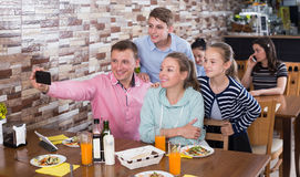 Adult family with teenage children taking selfie. Adult family of four with teenage children taking selfie in cafe Royalty Free Stock Photography