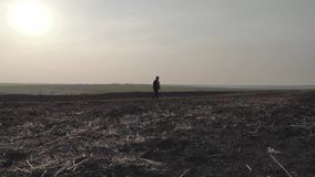 Adult farmer examining plowed field, preparing land for sowing. Seasonal agricultural works concept. Adult farmer examining plowed field, preparing land for stock video footage