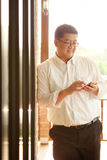 Adult Fat Asian man use smartphone after work outdoor Royalty Free Stock Photography