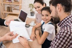 Adult father with wife and daughter signs sales contract in office of realtor. Concept of house selling. Confident realtor helps young family sell house stock photo