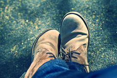 Adult feet with leather shoe. Lonely person feet with brown leather shoe in the outdoor Royalty Free Stock Image