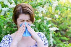 Adult female with allergic rhinitis about bird cherry blossoms Royalty Free Stock Photo