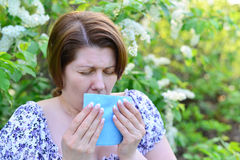 Adult female with allergic rhinitis about bird cherry blossoms Stock Image