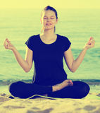 Adult female in black T-shirt is sitting and practicing asana Stock Photo