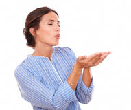 Adult female blowing to her left with palms up Stock Photography