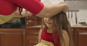 Adult female Caucasian hands putting cook hat on the head of little smiling girl. Happy daughter helping her mother with stock footage