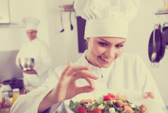 Adult female cook holding plate. Adult female cook wearing uniform holding plate with green salad Royalty Free Stock Photo