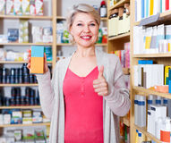 Adult female customer browsing rows of skin care products Royalty Free Stock Photography