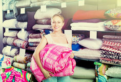 Adult female customer choosing blanket. In bedding section in shop Stock Images