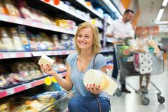 Adult female customer selecting cheese. In refrigerated section in hypermarket Royalty Free Stock Images