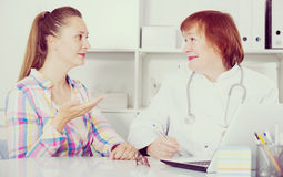 Adult female doctor leading medical appointment Stock Image