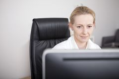 Adult Female Doctor Looking at her Computer Screen Royalty Free Stock Photos