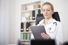 Adult Female Doctor Looking at her Tablet Screen Stock Photos