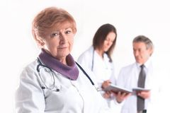 Adult female doctor therapist on blurred background of colleagues royalty free stock photos