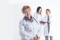 Adult female doctor therapist on blurred background of colleagues royalty free stock photo